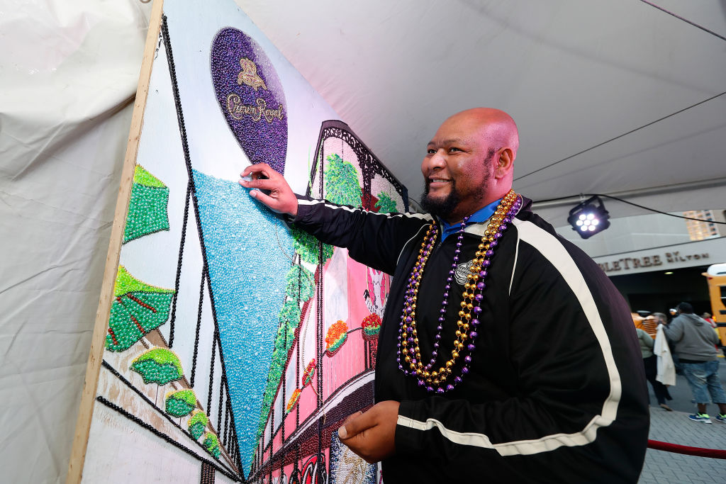 Former New Orleans Saints running back Deuce McAllister helps complete a bead mosaic