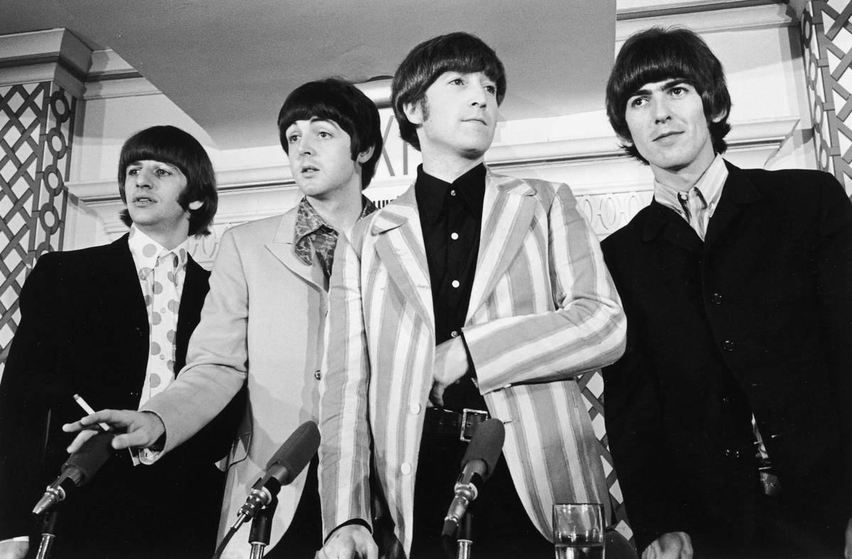 British pop group the Beatles standing in front of four microphones at a press conference where they discussed their concert at Shea Stadium, New York City.