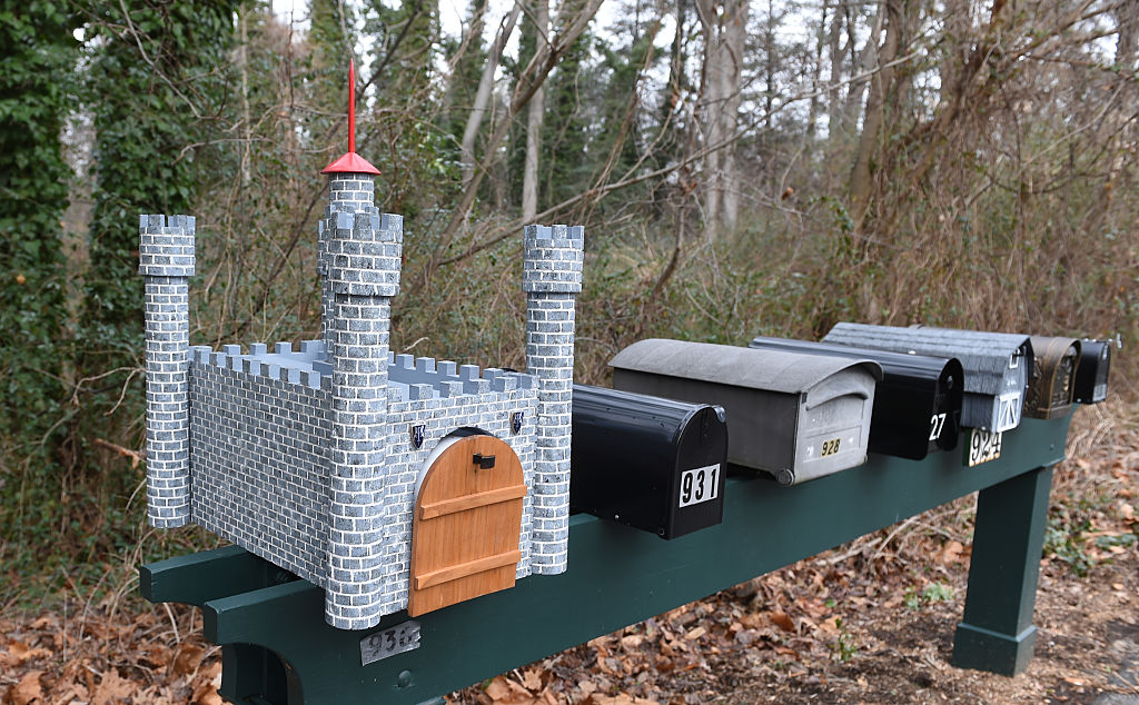 a castle-shaped mailbox on a post with six other plain mailboxes in front of trees