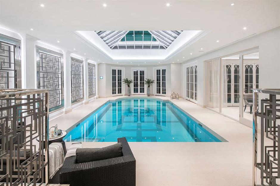 A large swimming pool fills the space of the white room.