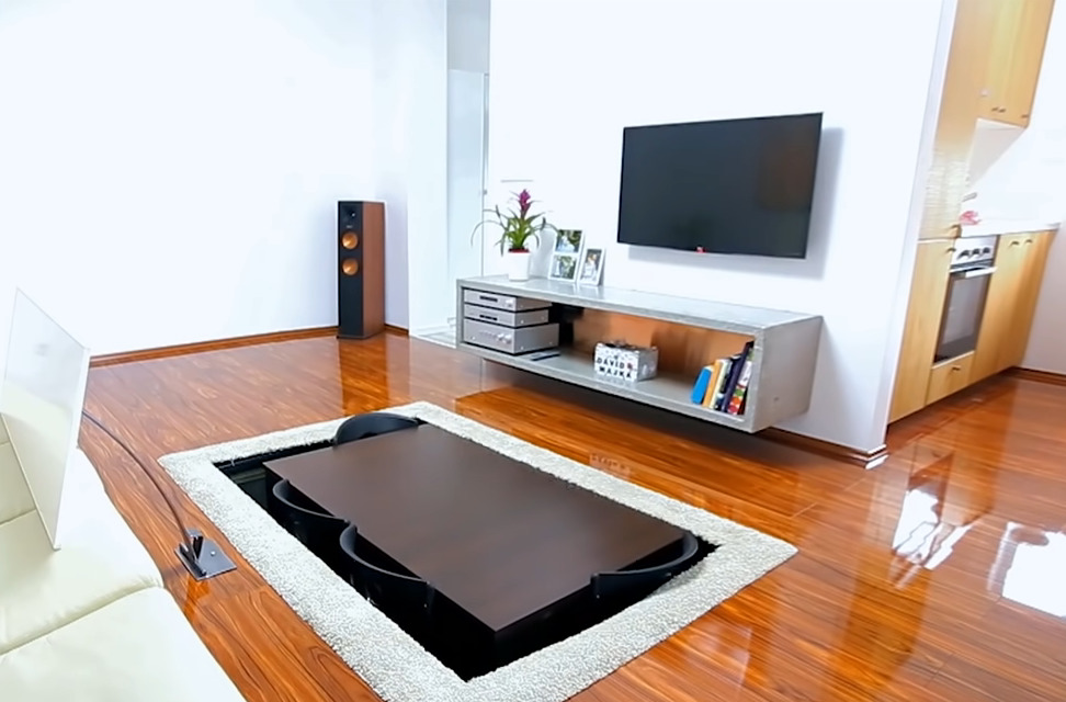 A table and chairs lift out of a space in the floor that was previously covered by a rug.