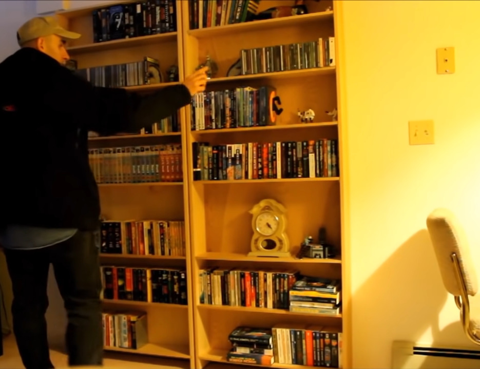 A man stands in front of two bookshelves and appears to be pushing a button.