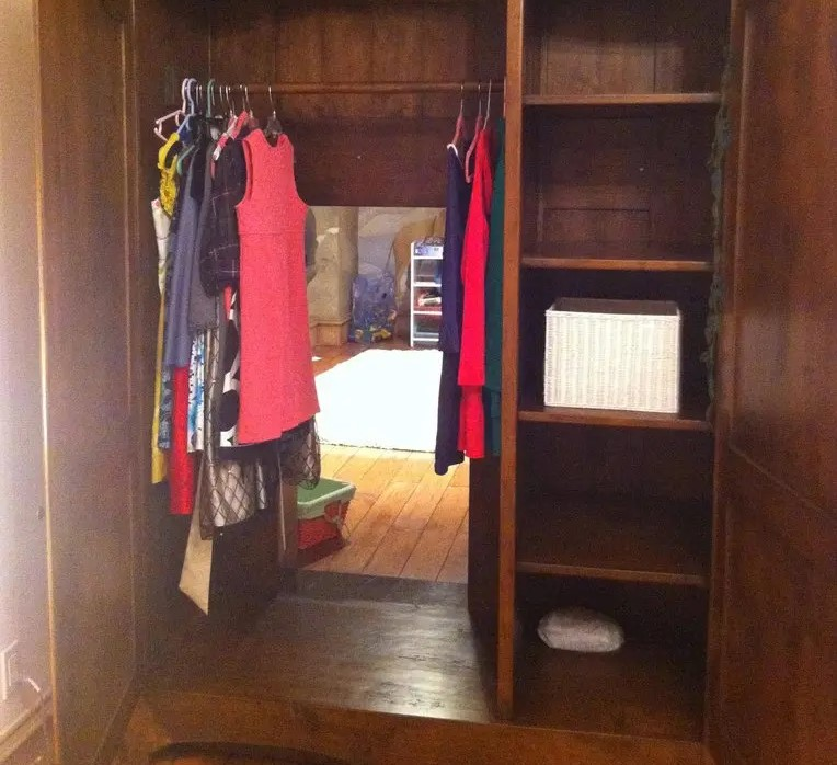 An opened cabinet reveals a passage into another room.