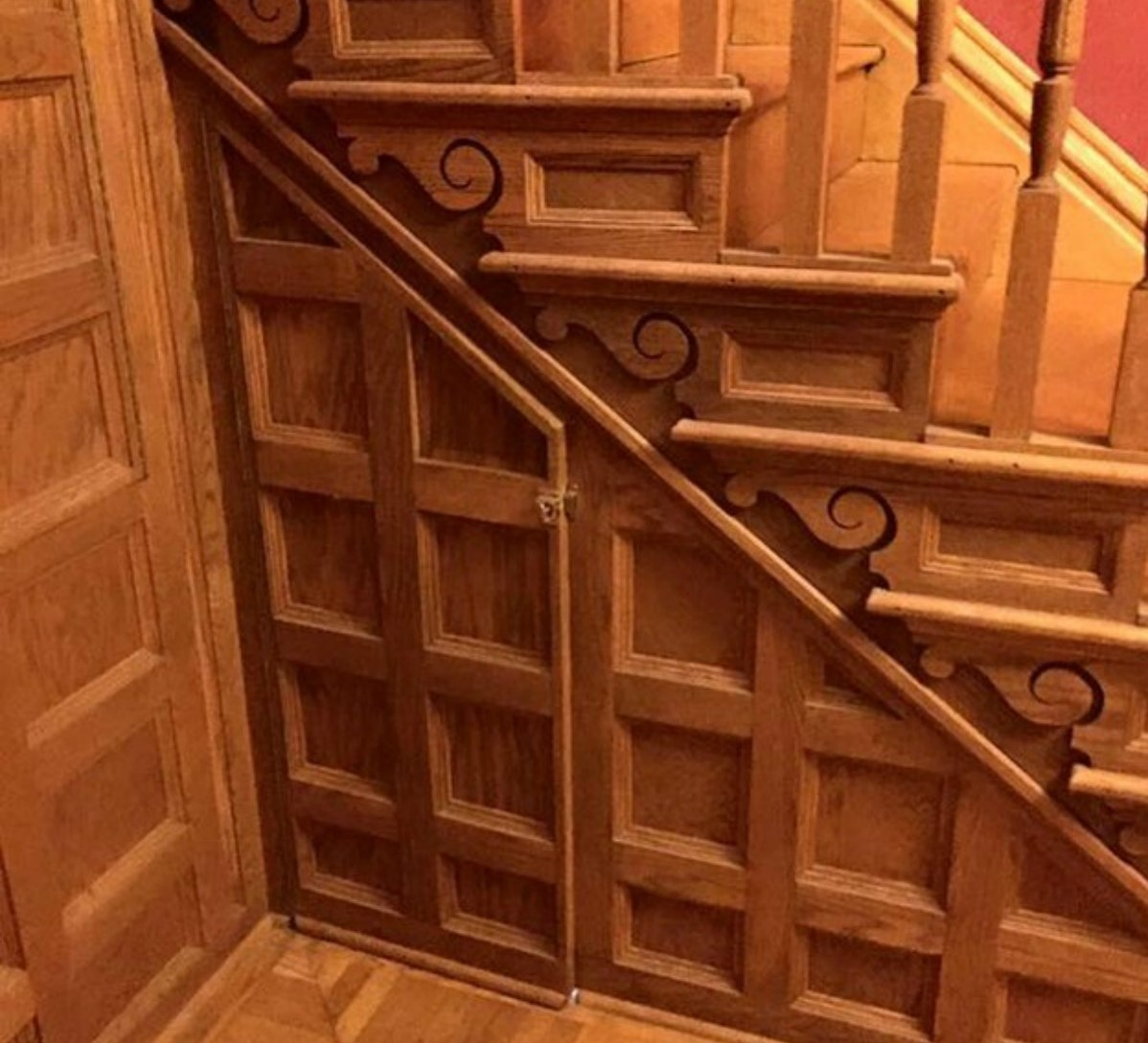 A staircase with careful woodwork appears to have an opening.