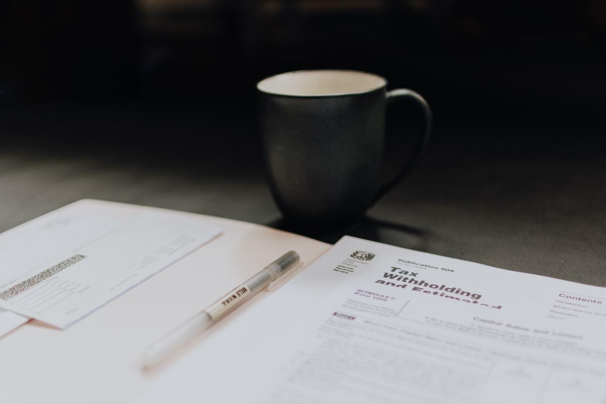 photo of tax forms and mug