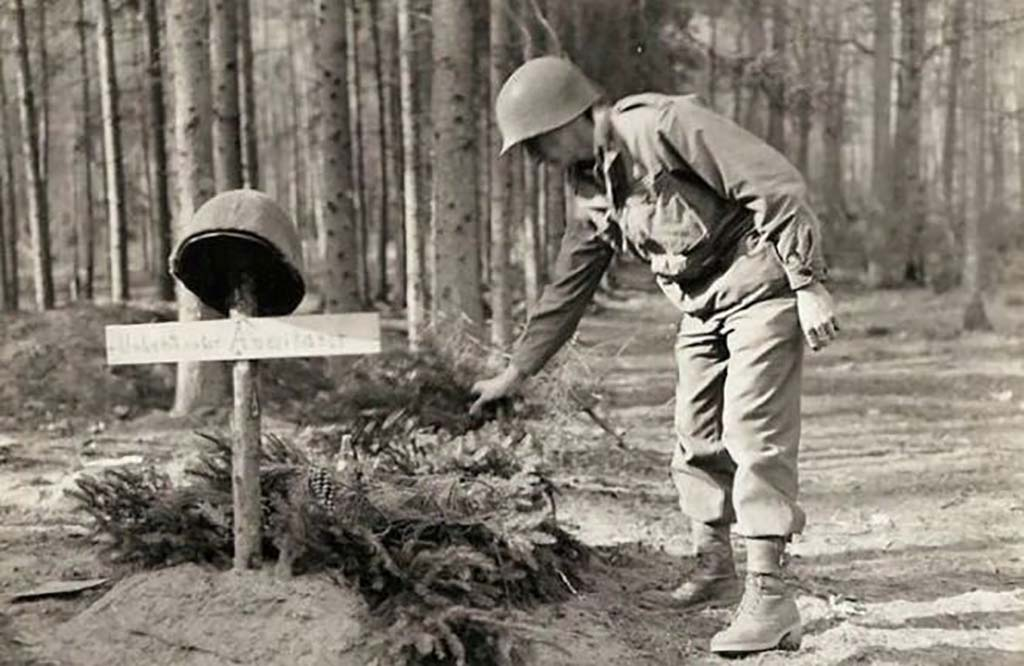 Soldier putting wreath on grave