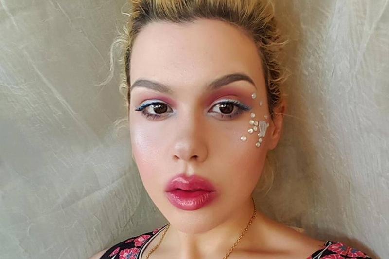 Amber wears face jewels and colorful makeup.
