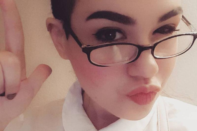 Amber purses her lips and wears glasses in a selfie.