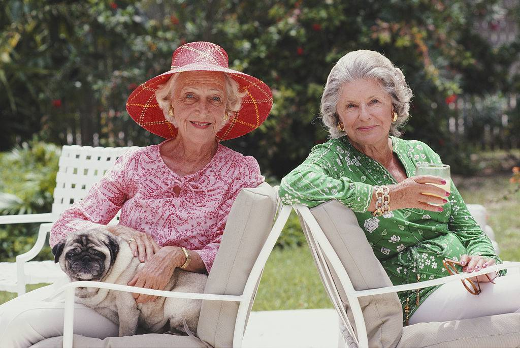 two senior women sit on patio with pug on lap