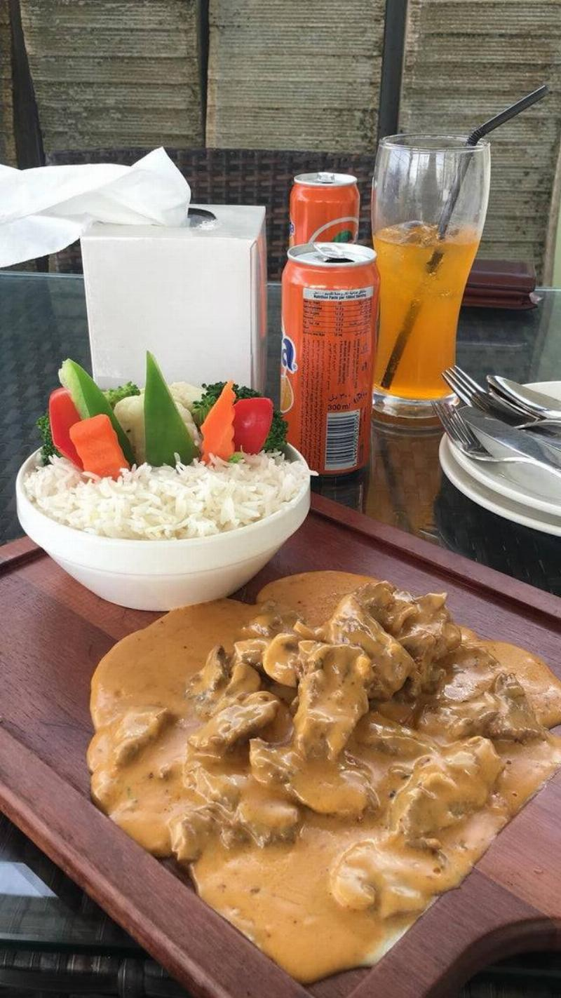 Curry on a chopping board with rice in a bowl