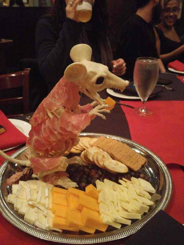 charcuterie with meat served on fake mouse skeleton