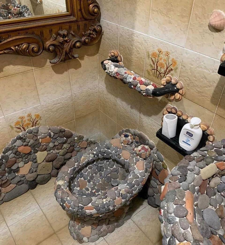 bathroom surfaces including toilet decorated with rocks